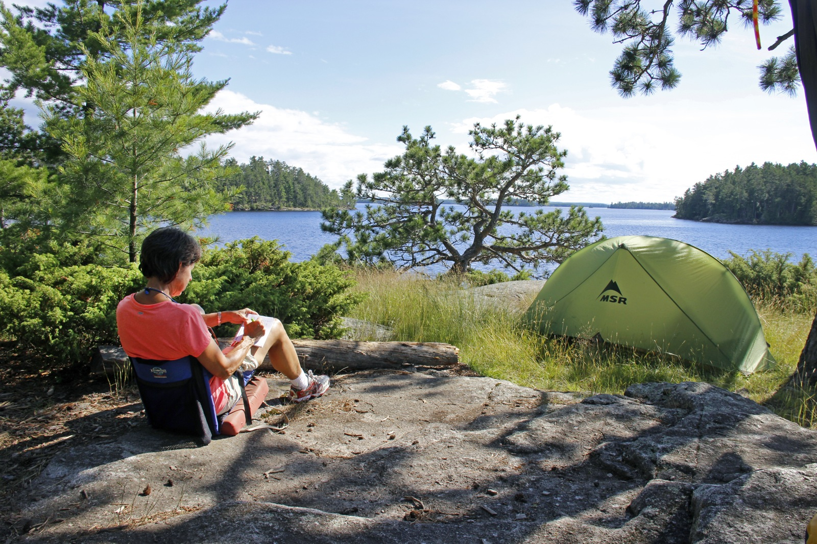 a woman sits on a rock with a journal by her tent with a view of the lake and distant islands