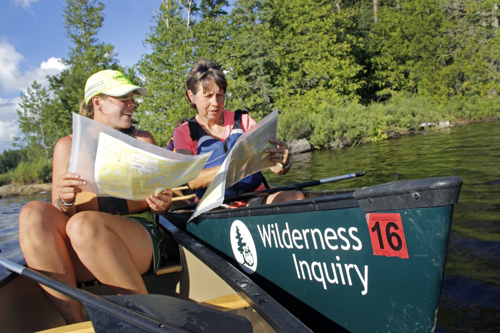A guide and a participant compare maps while sitting in separate canoes.