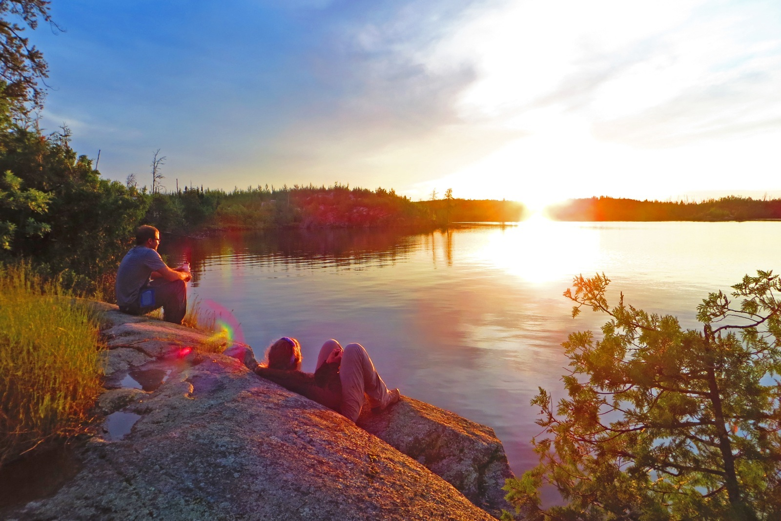 two participants sit on a rock by the lake enjoying the yellow and blue sunset