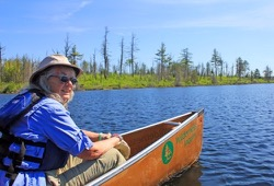 A woman takes a break from paddling in the BWCA.