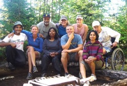 a group photo of participants sitting on a log at the campsite