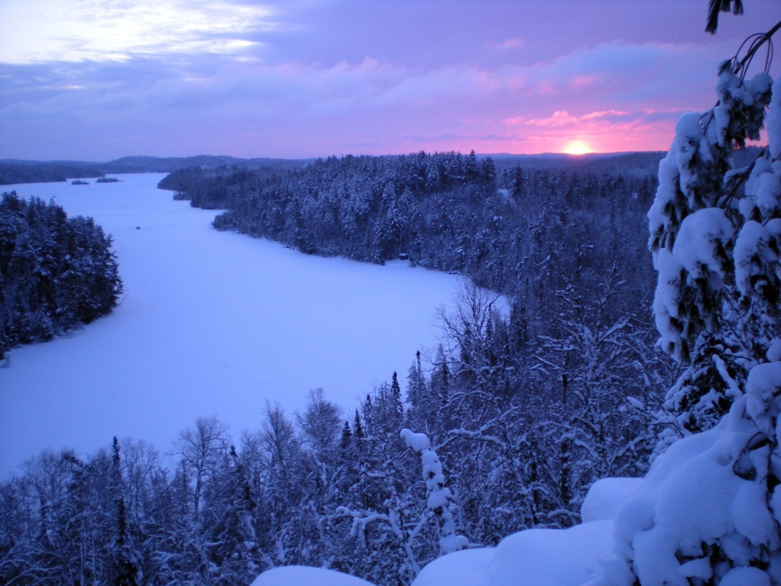 The winter sun rises over the snow-covered, frozen West Bearskin Lake that's surrounded by snowy trees.
