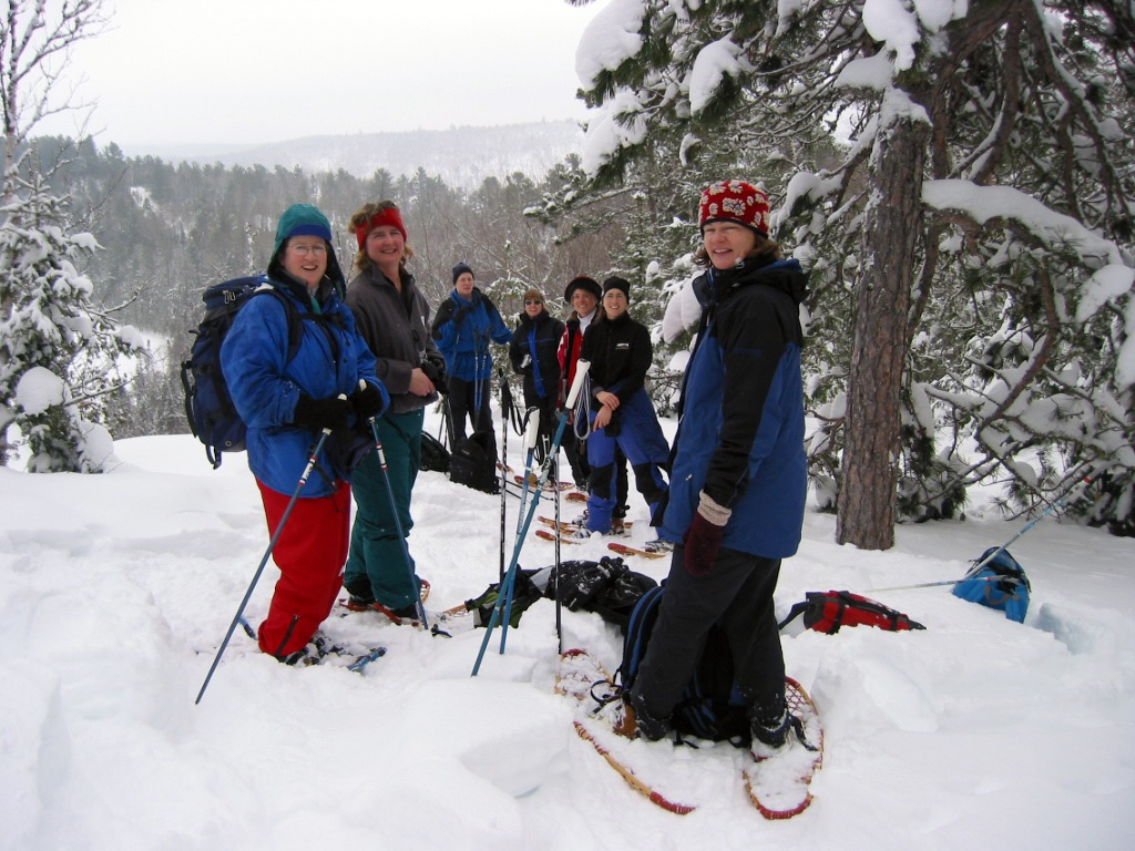 Surrounded by snowy evergreen trees, a group of snowshoers gathers to take in the view of Rose Falls on Rose Lake.