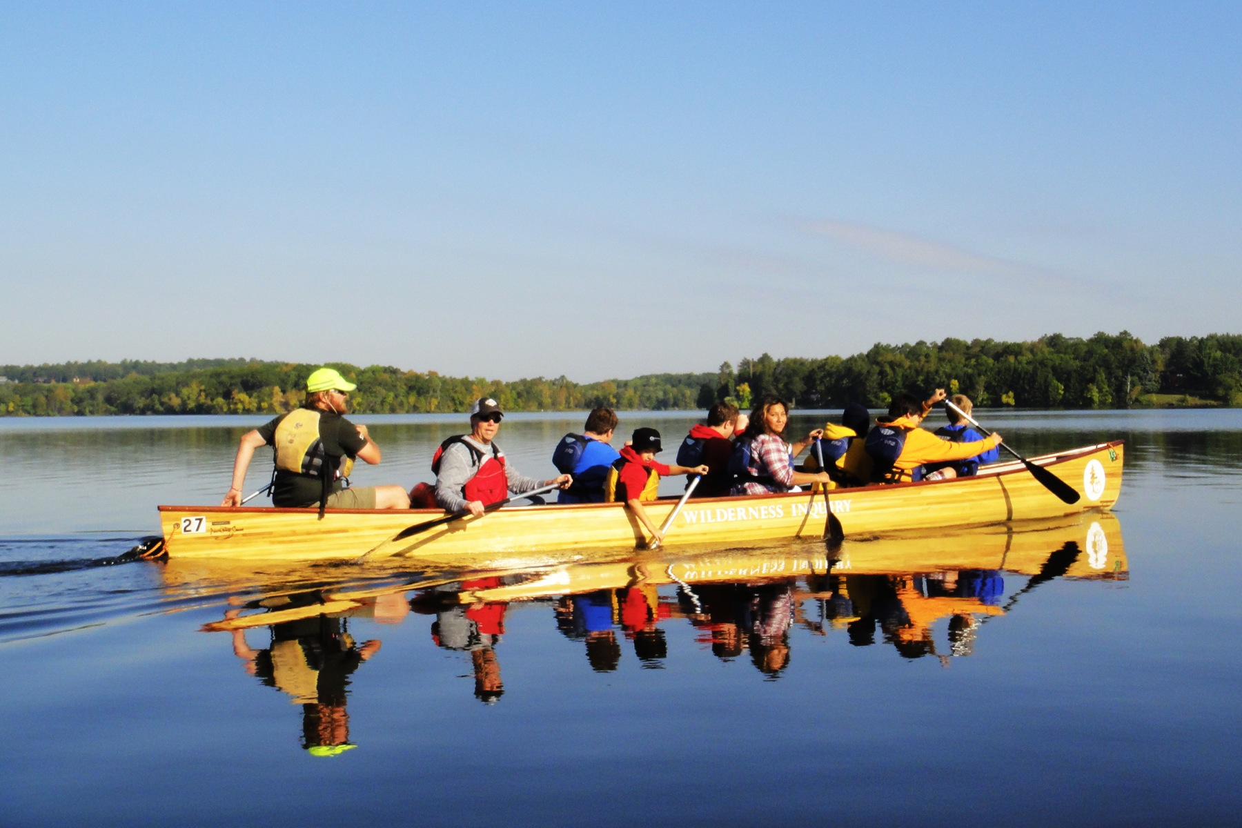 a group of 9 paddle the canoe on a calm sunny day on the Mississippi River