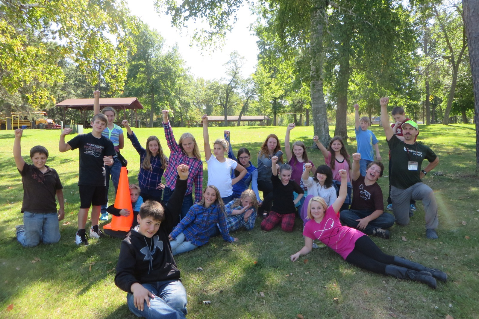 group photo of students and staff with one arm up pointing towards the sky in a park after canoeing the Mississippi