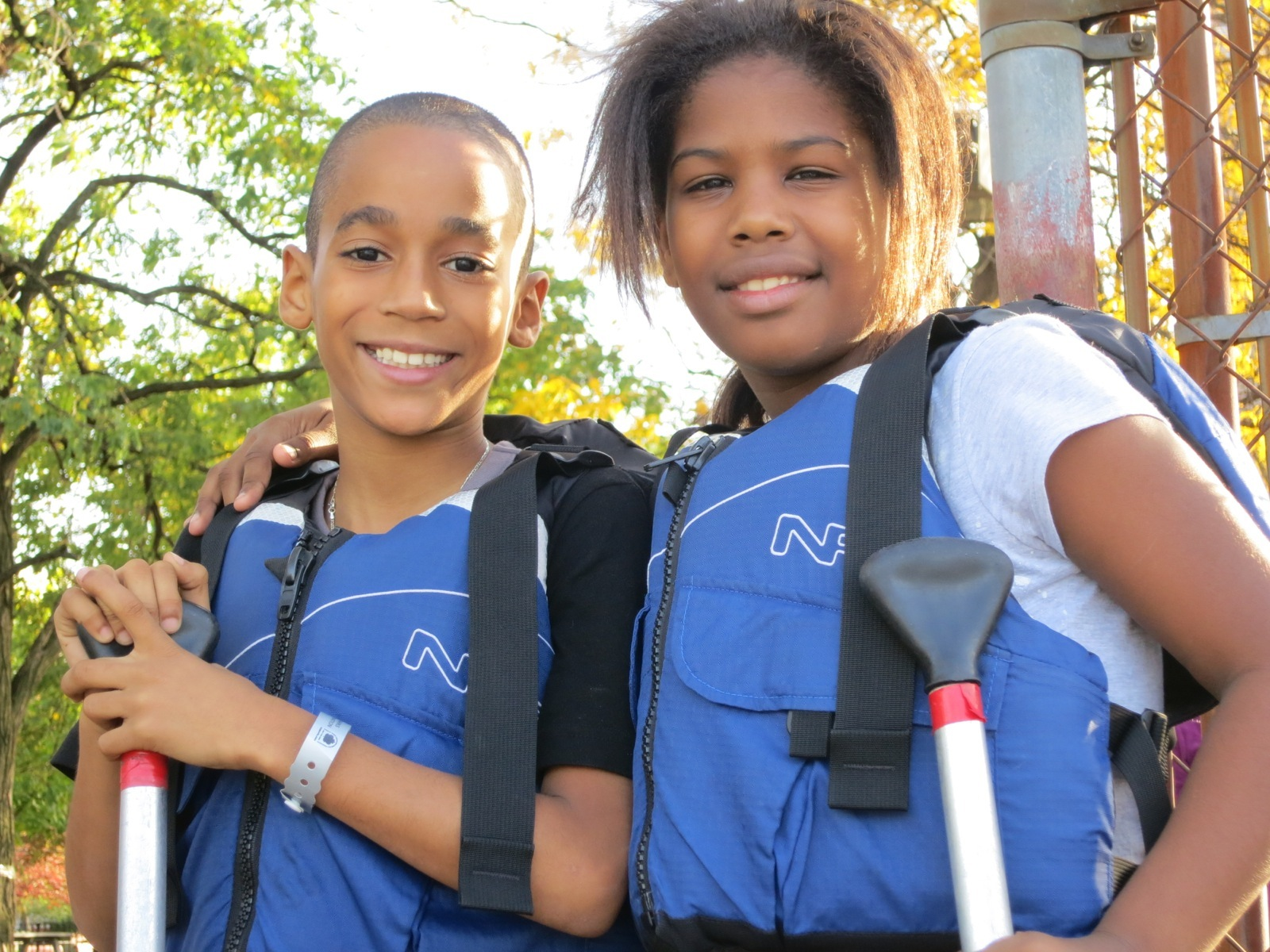a girl and boy wearing their life jackets getting ready to get in the canoe
