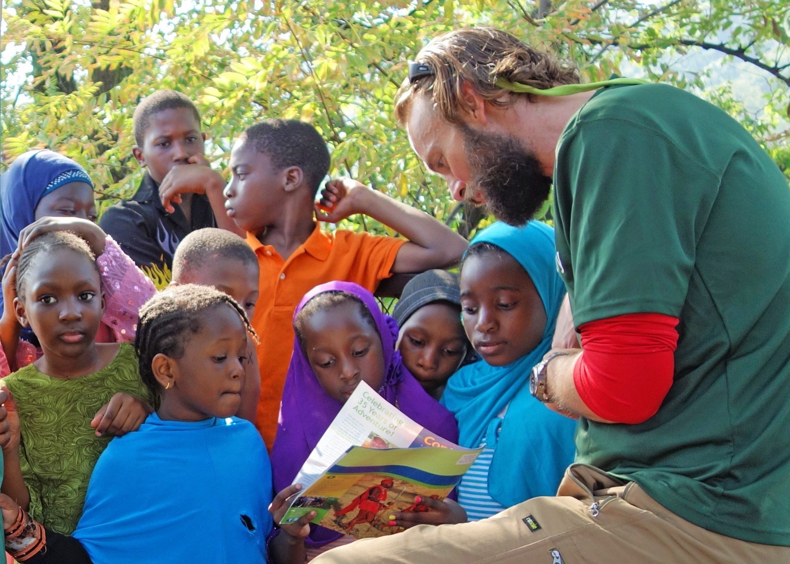 a group of children learn about different WI trips with a crew member in the outdoors