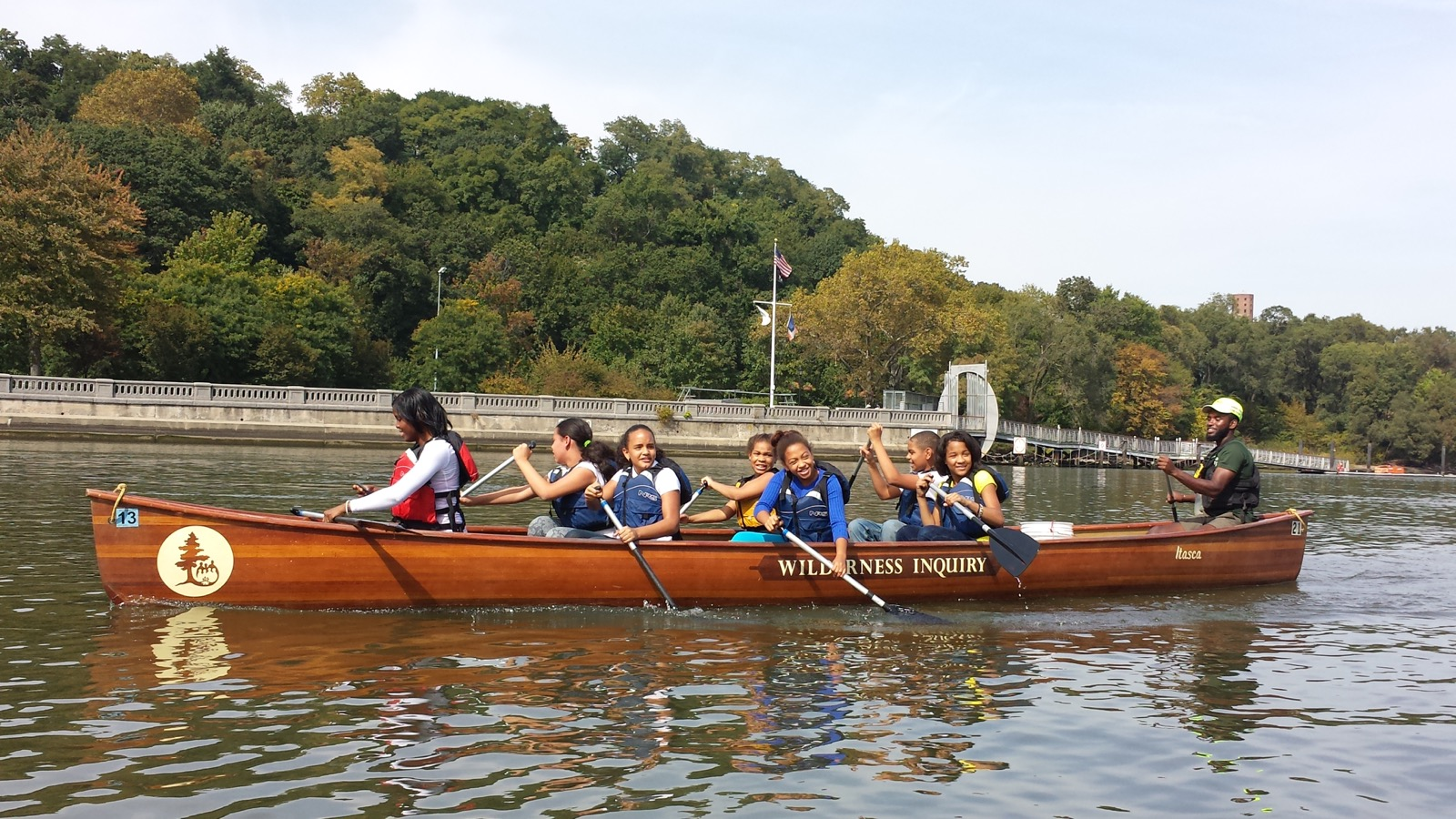 a group of youth help paddle their canoe up the Harlem River