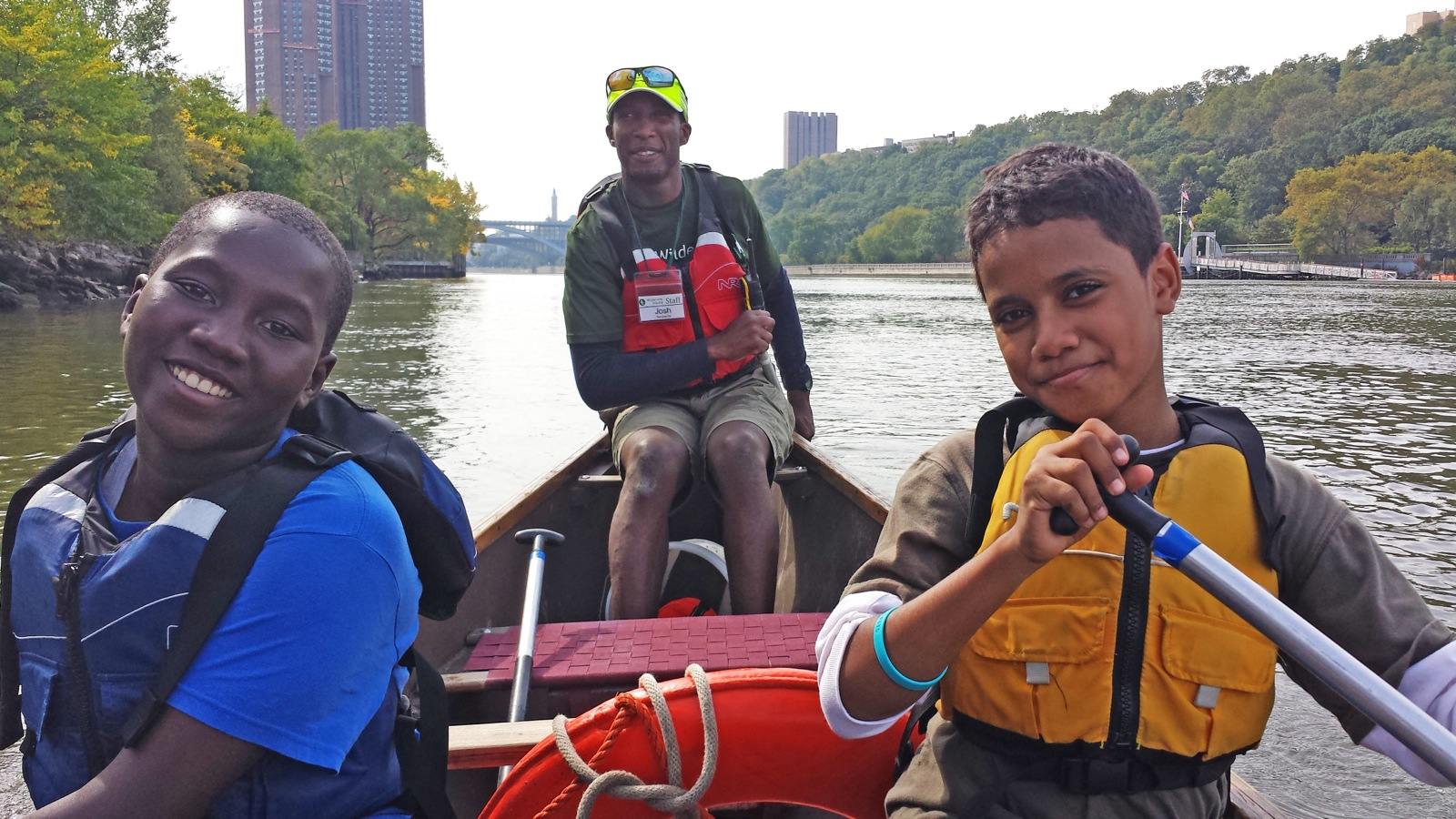 two boys in the middle smile for a photo with a staff member in the stern of the canoe on the Harlem river