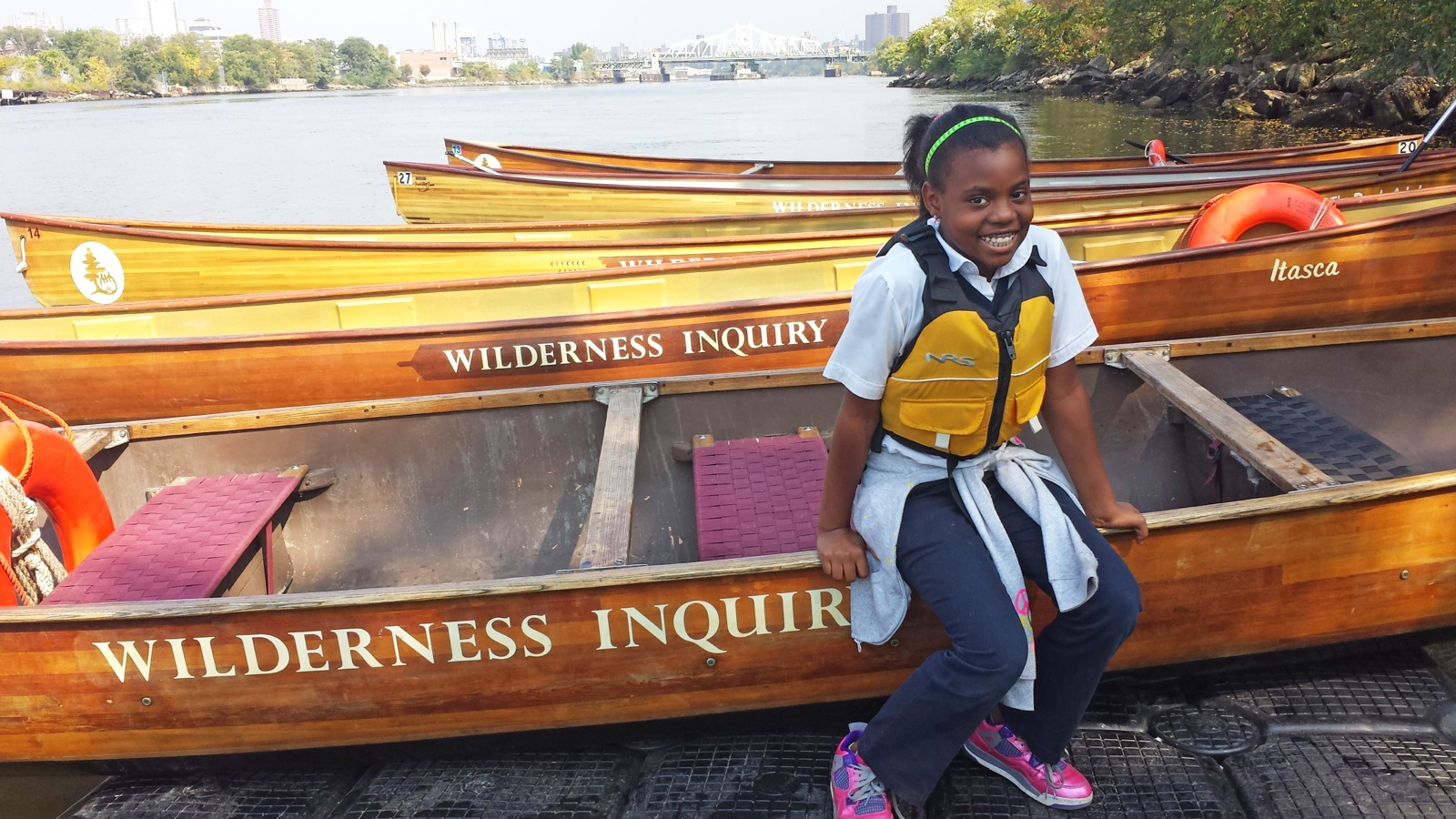a girl sitting on the edge of a canoe at the docks smiling for the camera
