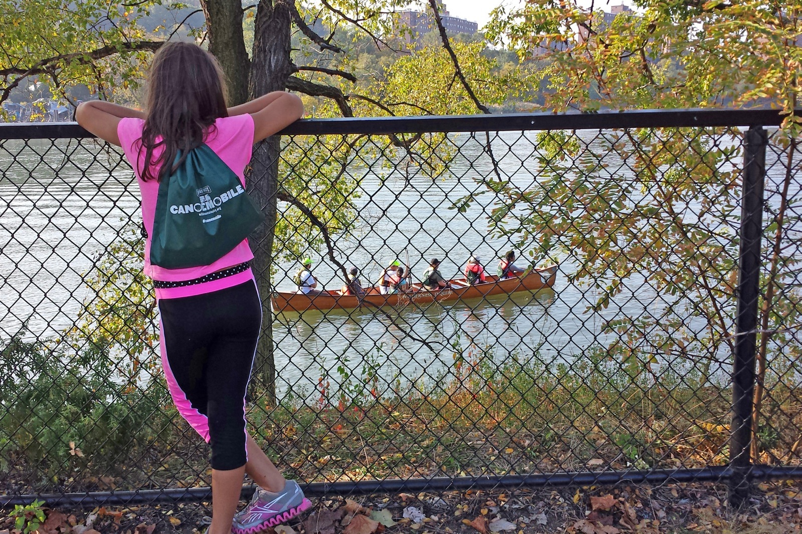 a young participant faces the lake away from camera as a Voyageur canoe passes by on the Harlem River