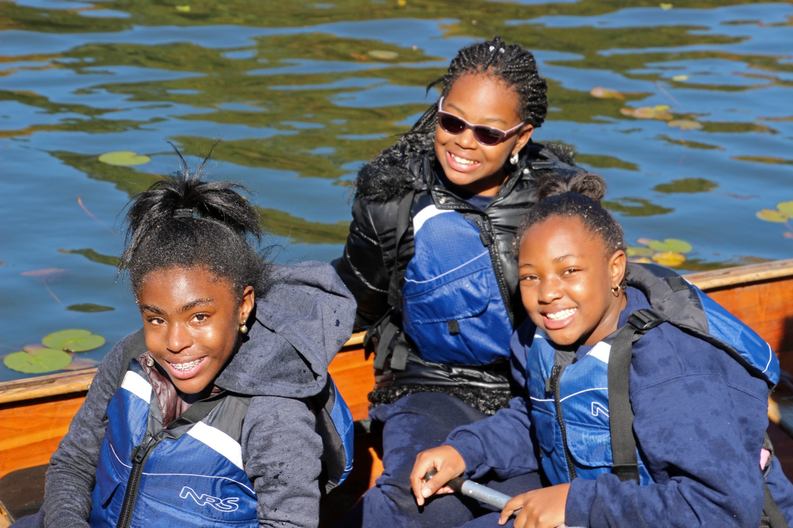 three participants smile for the camera while in the canoe on the Harlem River