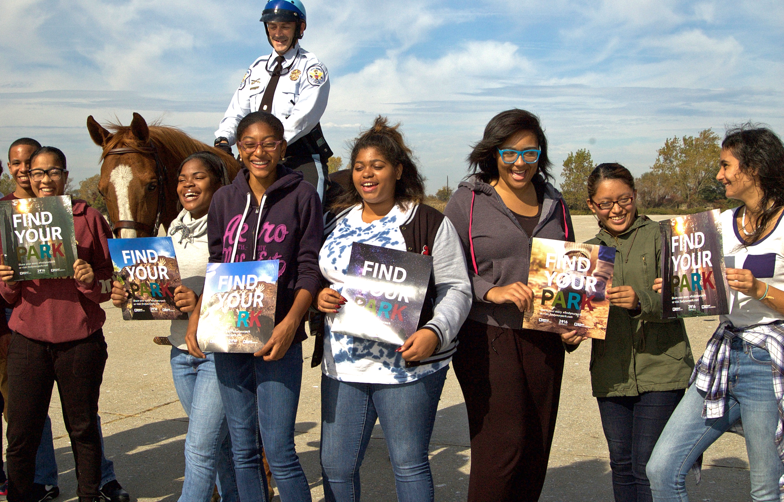 8 participants smile for the camera while holding a Find Your Park magazine