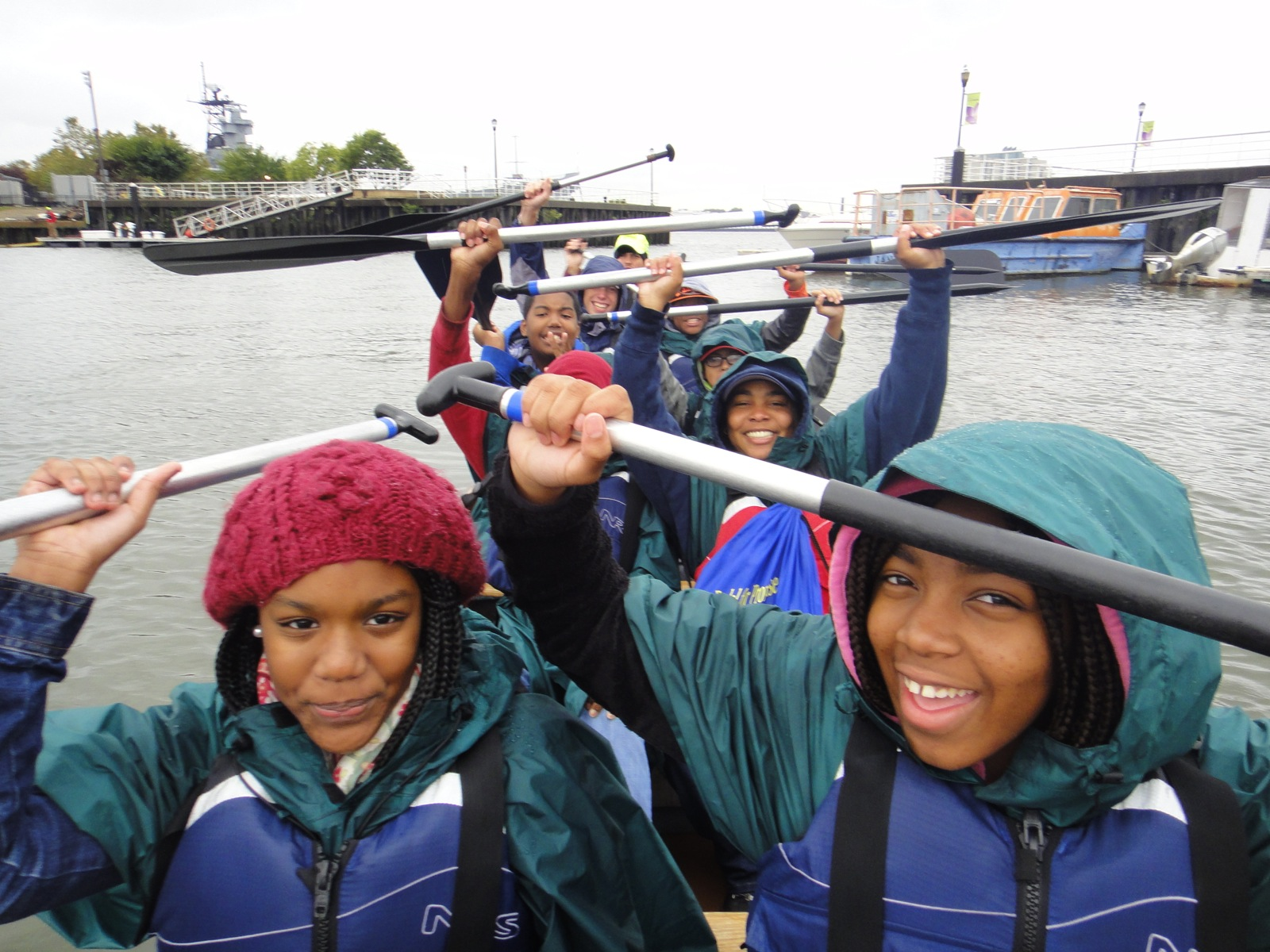 Participants hold their paddles above their heads in the canoe on a rainy day on the Delaware river