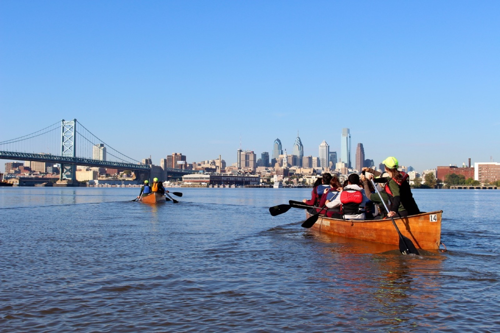 two groups paddle their canoes on the Delaware River with the skyline in the background