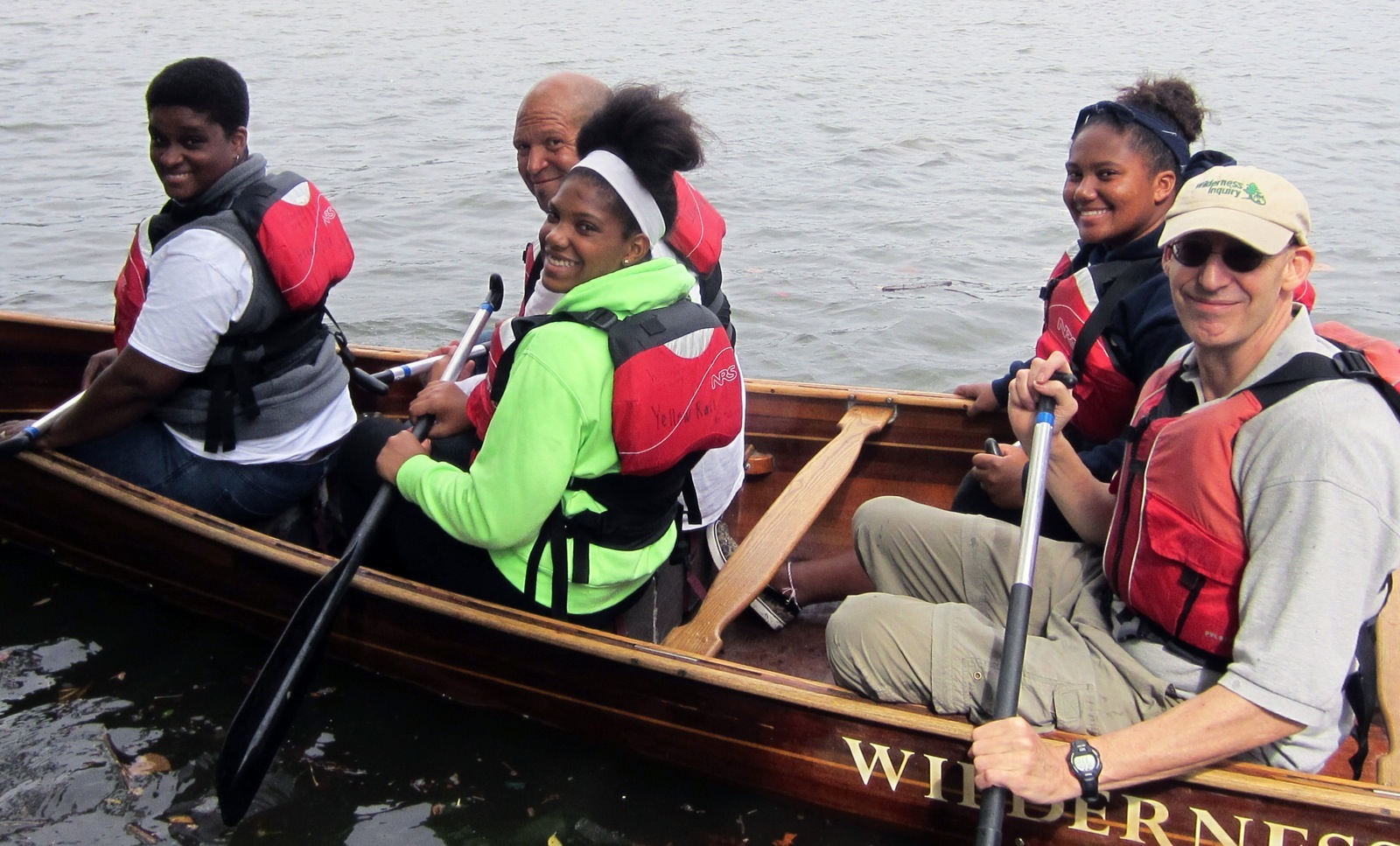 5 participants paddling in the bow of the canoe smile for a photo on the Delaware