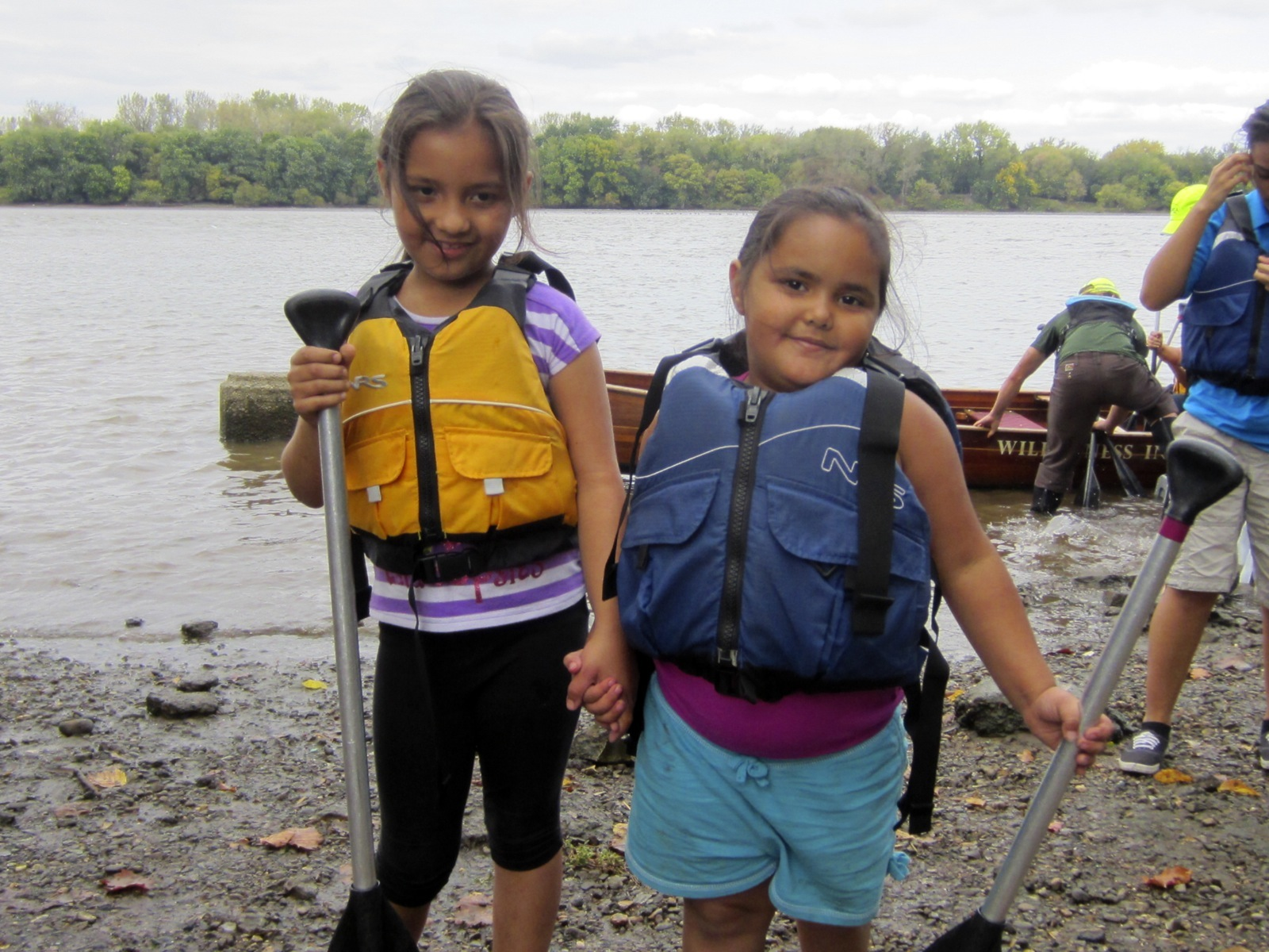 two young girls hold hands on the shore with their paddles