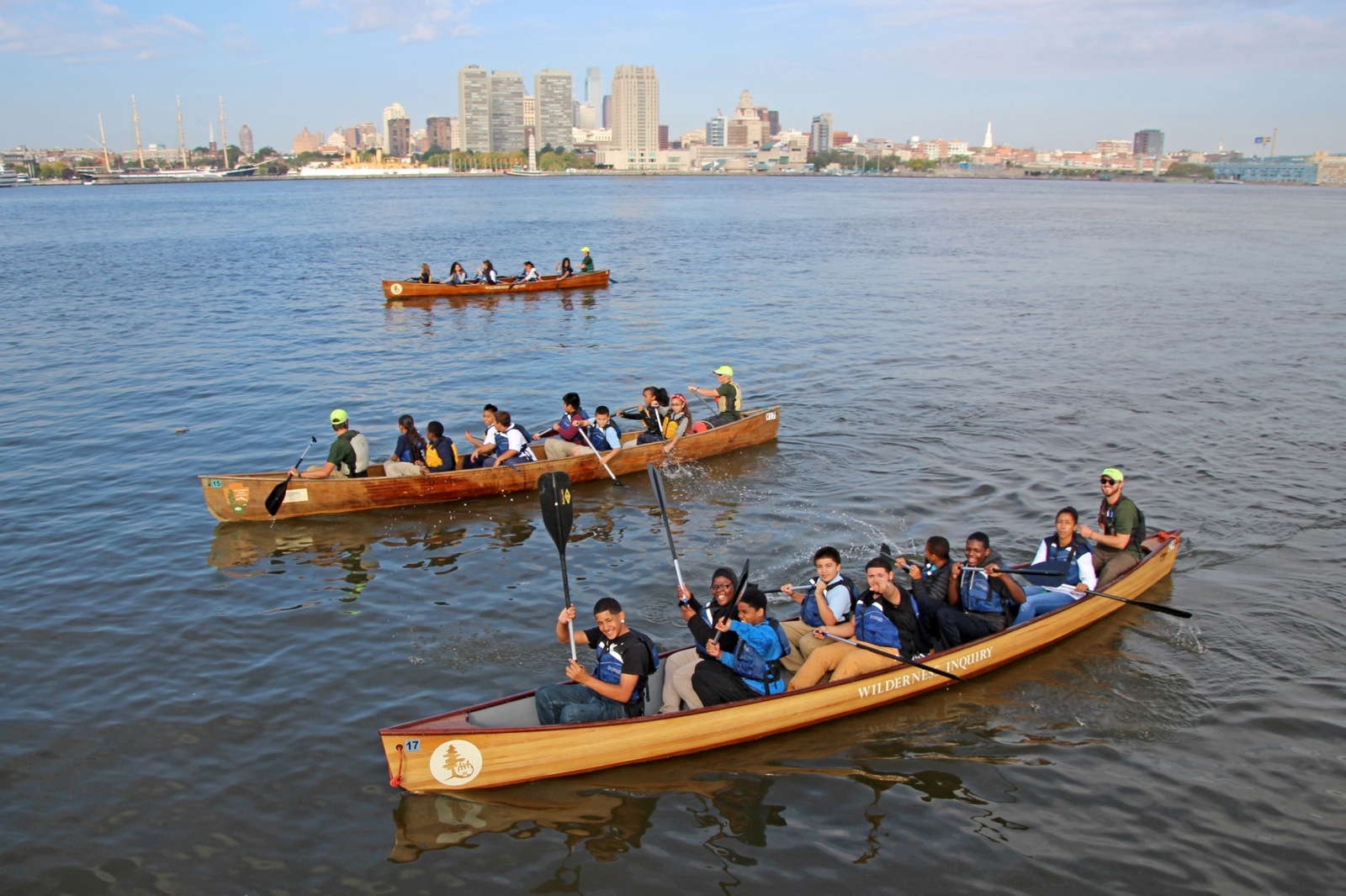 three canoes paddle along the Delaware River with the city skyline in the background
