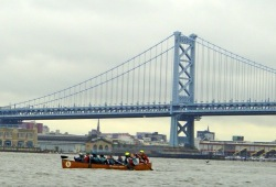 a group paddles their canoe by the Ben Franklin Bridge