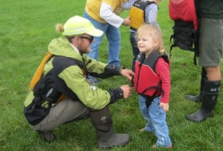 Staff member helps young girl with life jacket in Camden