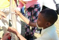 A young student tests the water quality in Delaware River