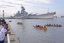 a group of canoes paddle beside a battle ship in a marina on the Delaware River