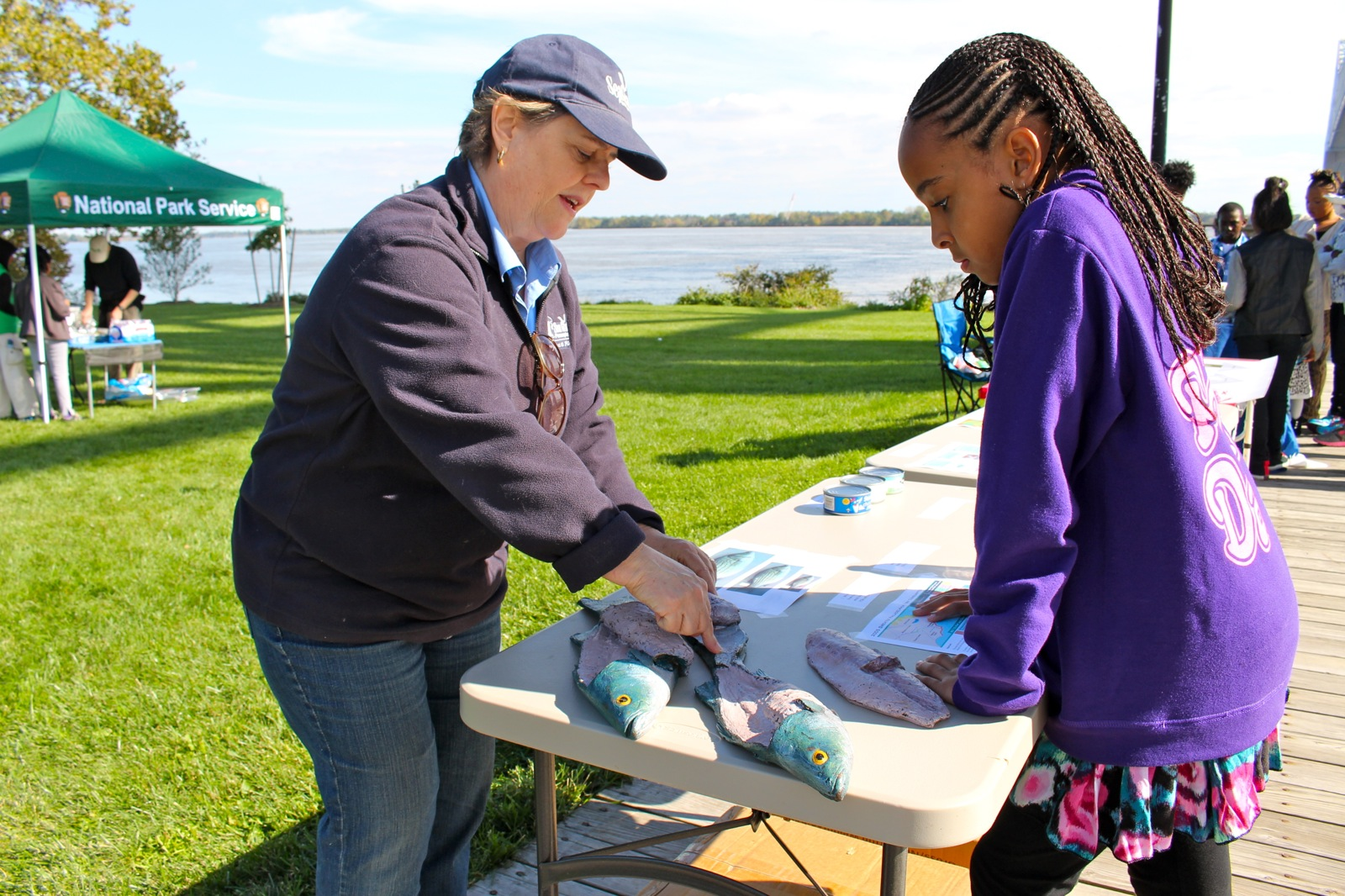 A student learns about fish dissection by the Delaware River