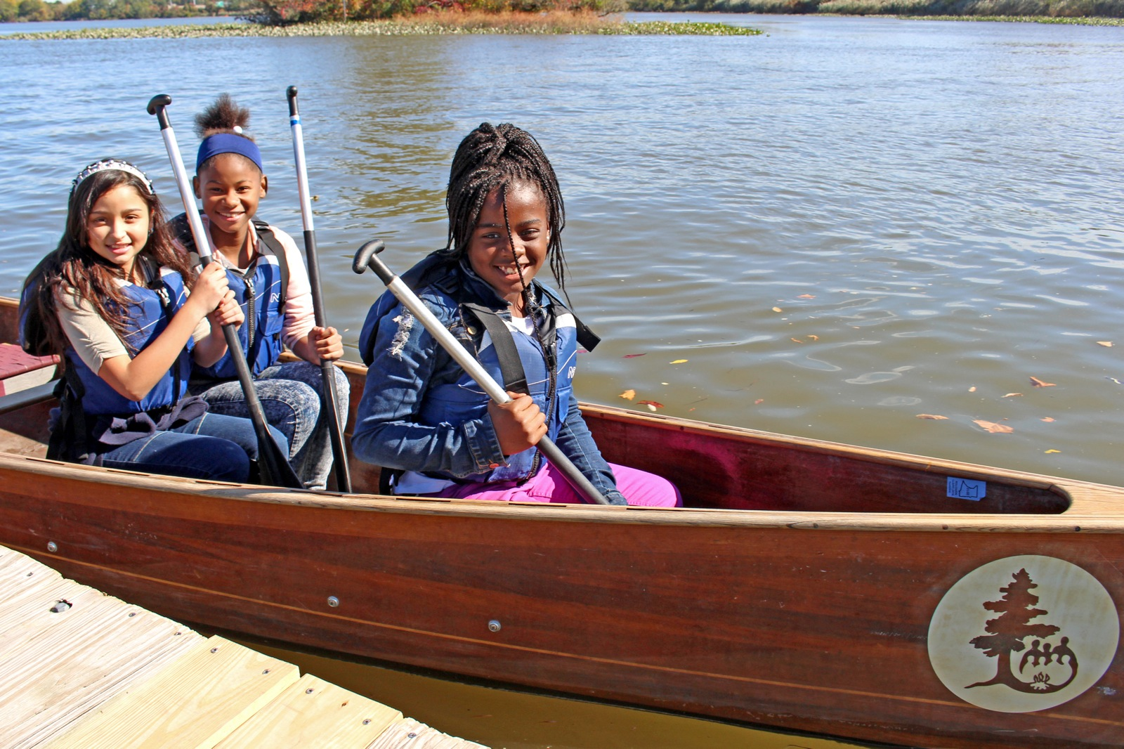 three girls sit near the bow of the canoe as they wait for the rest of the group to load into the canoe