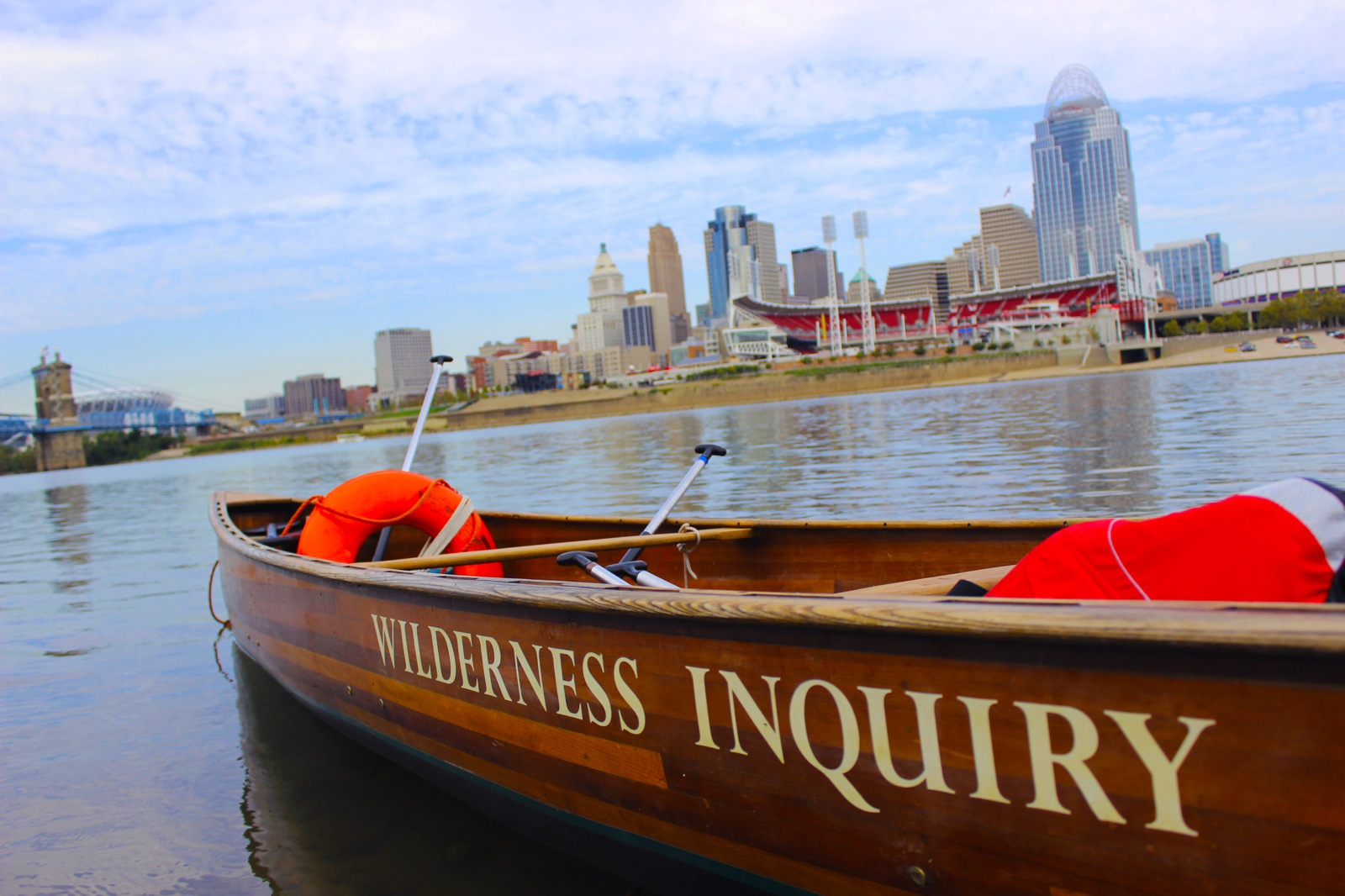 a photo of an empty canoe on the water with the Cincinnati skyline in the backdrop