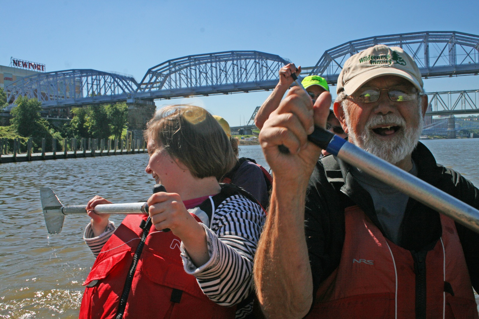 two participants smile as they paddle their canoe down the Ohio river