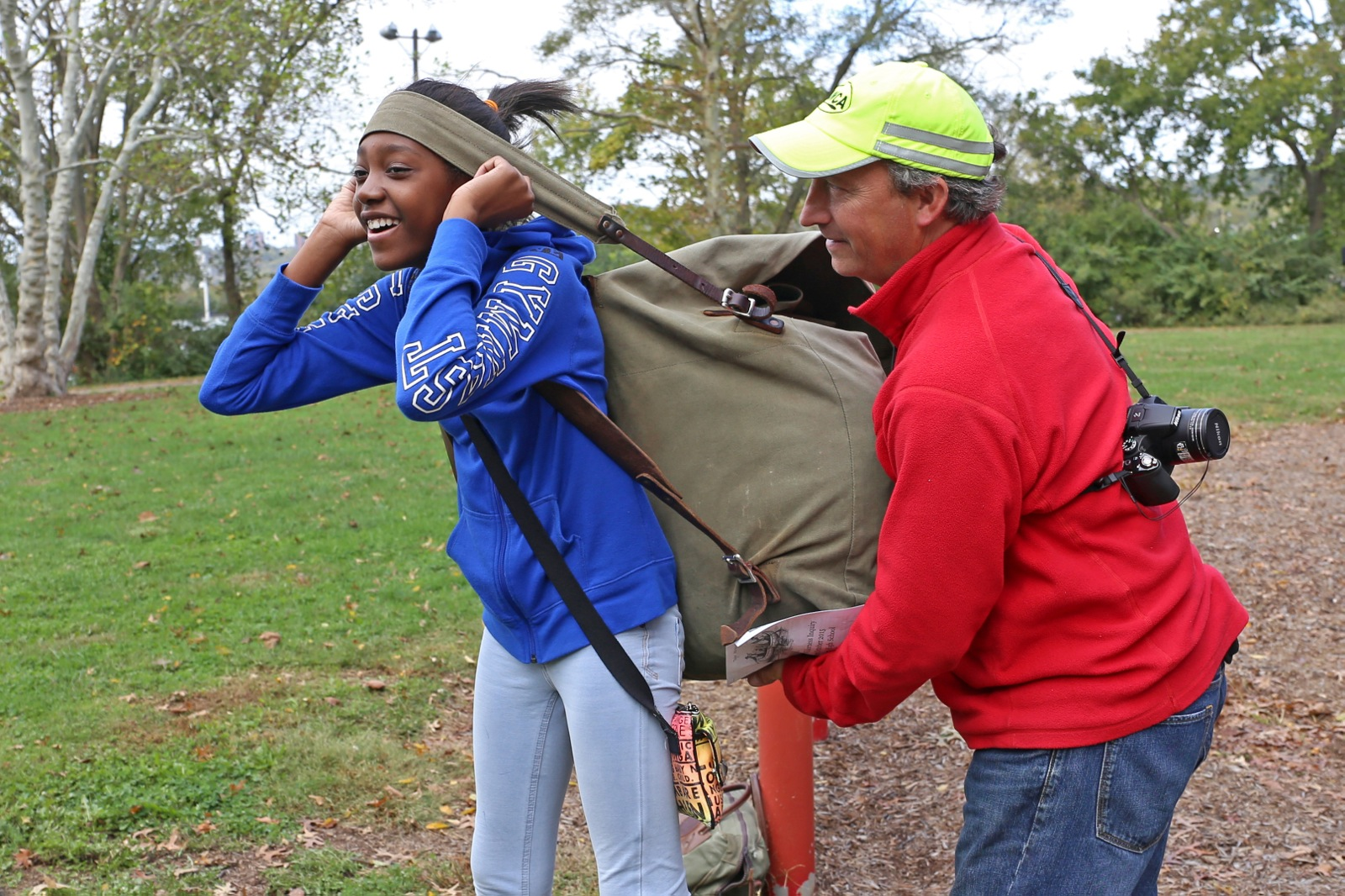 a participant carries a large back pack across a field while a staff member helps