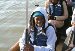 A participant smiles for the camera as they are about to paddle along the Ohio River