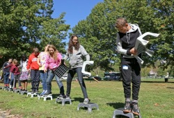 Students use stools and team work to get across a piece of land without touching the ground in Cincinnati