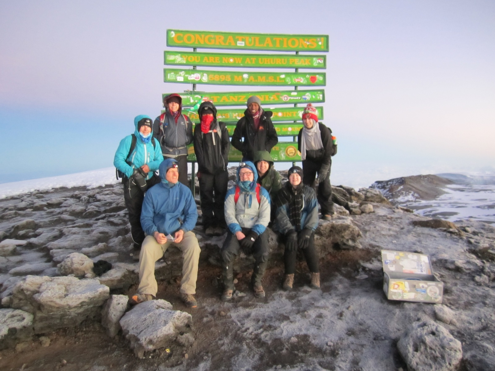 "A group stands in front of a ""Congratulations!"" sign at the rocky, snowy summit of Mt. Kilimanjaro."