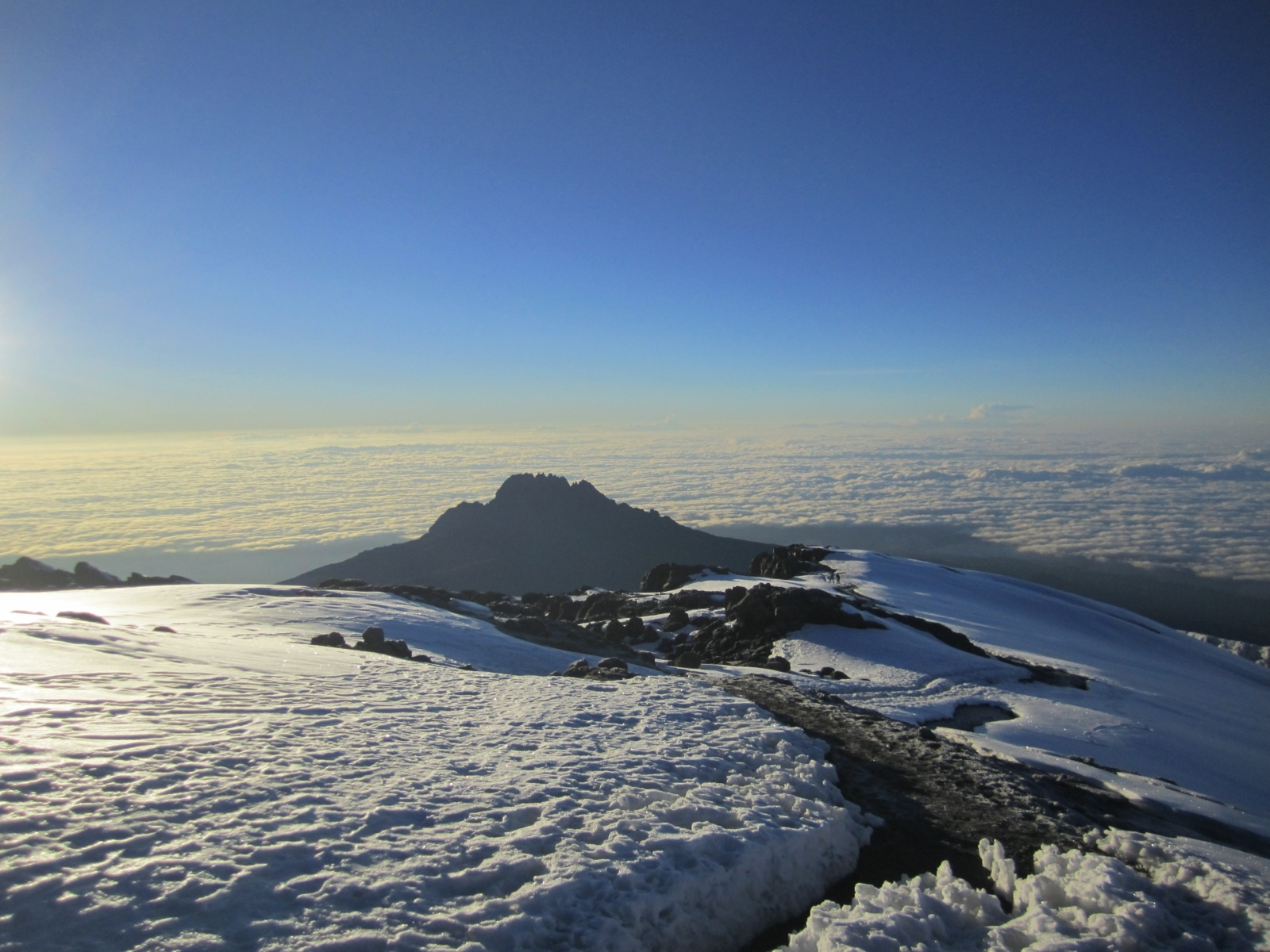 A rocky, snowy landscape in the foreground with a view out over the clouds from the summit of Mt. Kilimanjaro.