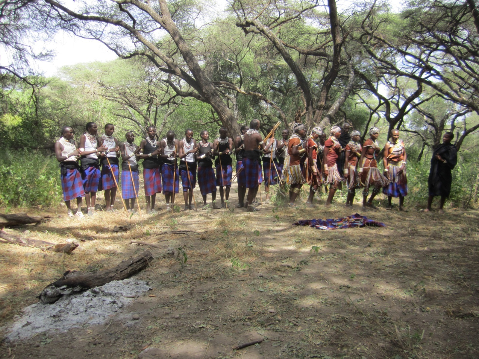 A group of Maasai people wearing Shuka, traditional red and blue plaid skirts, and beaded jewelry.