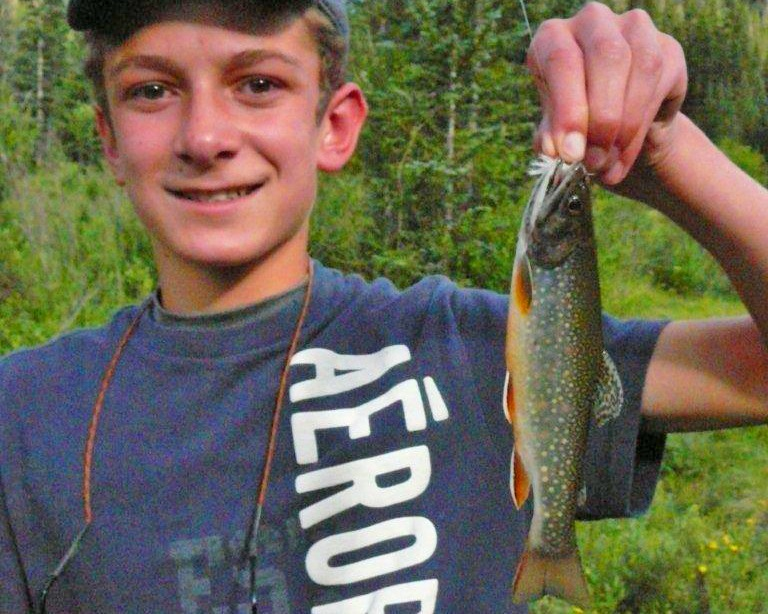 A young man holds up the small trout he caught.