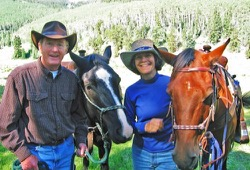 Kevin and Martha Milbery stand with their horses as they prepare for the day.