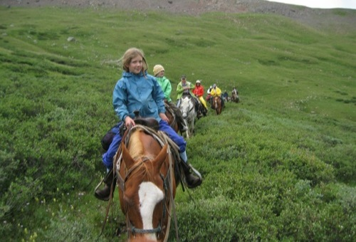 The line of horseback riders make their way up a grassy trail to the Continental Divide in the Rocky Mountains.