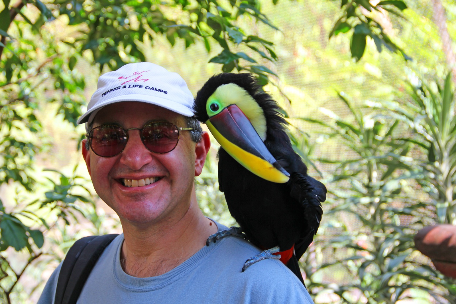 A man with a colorful toucan sitting on his shoulder.