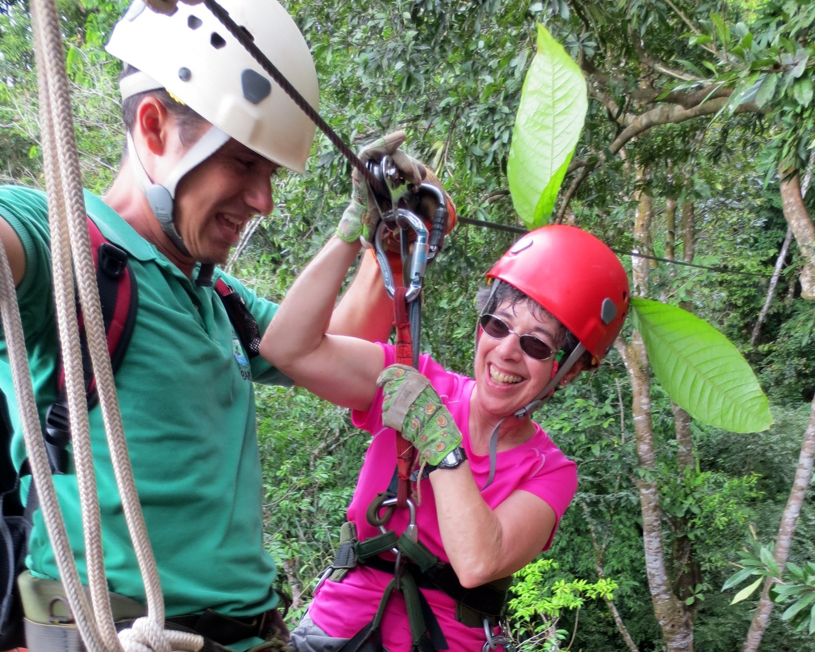Woman gets ready to ride a zipline with help from a guide.