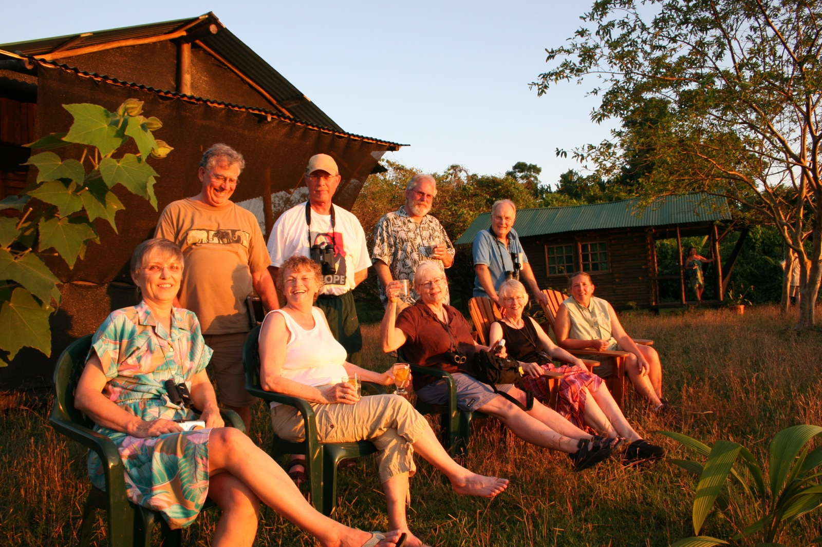 a group of nine participants watching the sunset in front of the log cabins