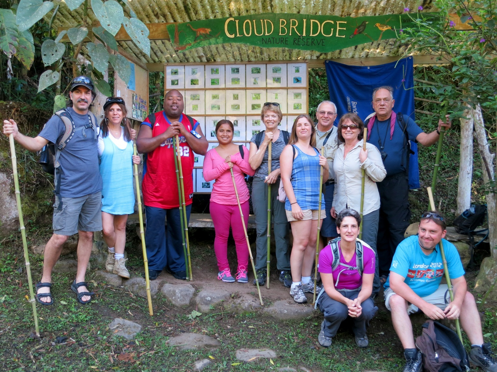 Group of 11 smile in front of the Cloud Bridge Nature Reserve sign with their hiking sticks