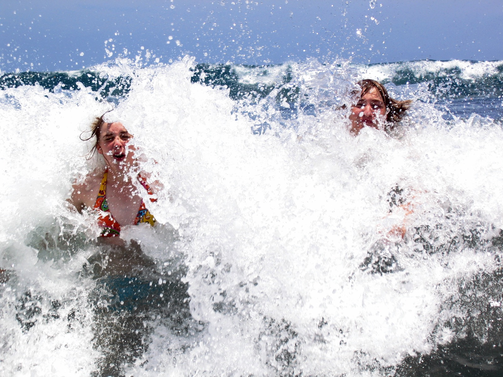 Two young girls play in the ocean