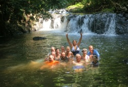 Group of 12 swimming below a waterfall in the jungle.