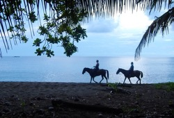two participants ride horses along the beach