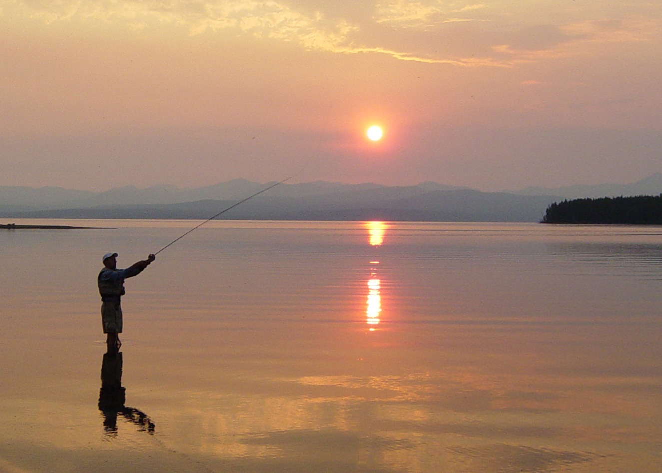 A participant fly fishes on Yellowstone Lake as the the sun rises.