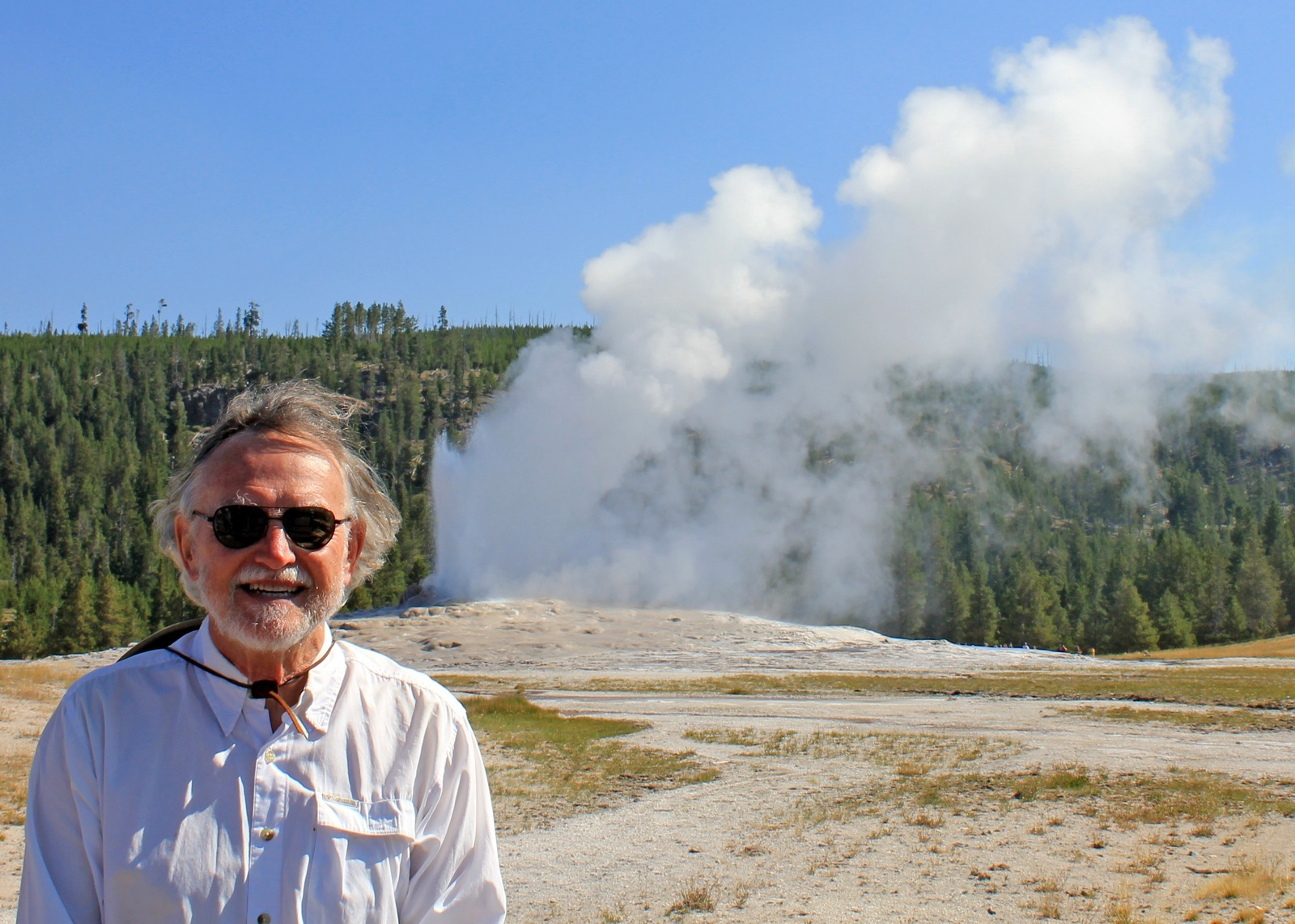 A man poses for a photo in front of a geyser in Yellowstone National Park.