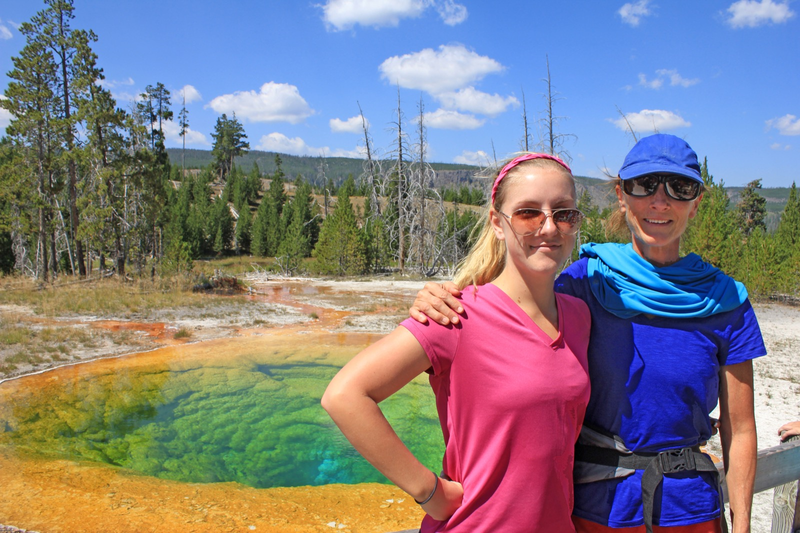a mother and daughter smile beside a green blue and orange colored thermal pool on a sunny day