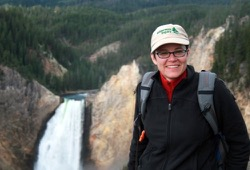 A woman smiles for a photo with the Yellowstone waterfalls in the background